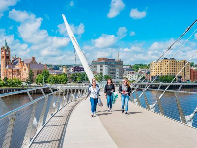 Young adults cross The Peace Bridge over River Foyle in downtown Derry, Northern Ireland, United Kingdom on a sunny day.