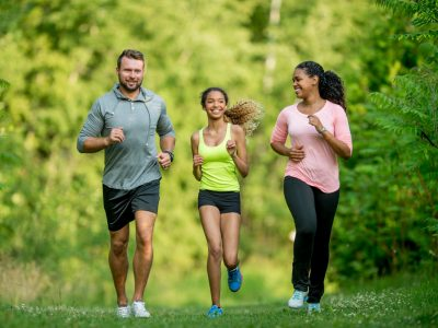 A multi-ethnic family (mother, father, daughter) getting exercise by going for a jog at the park.