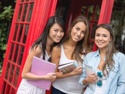 Happy multi-ethnic group of women studying English in London and looking at the camera smiling
