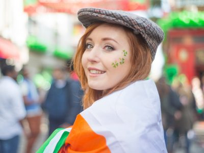 Smiling pretty red haired Irish girl with tweed hat, wrapped in the Irish flag and shamrocks painted on her face, Temple Bar, Dublin, Ireland.
