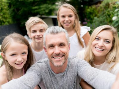 Happy Caucasian family taking a selfie outdoors and looking at the camera smiling