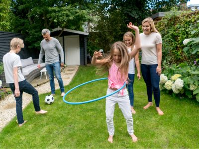 Happy family watching their girl playing with the hula hoop outdoors and enjoying the summer