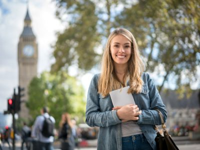 Happy female student in London holding a tablet computer and looking at the camera smiling